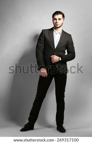 Elegant man in suit on gray background - stock photo
