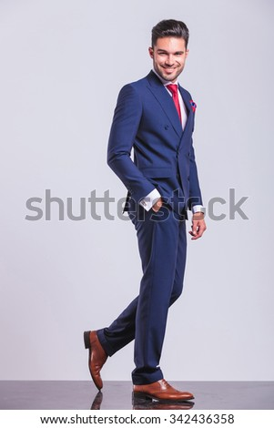elegant man in suit walking away with hand in pocket while posing  - stock photo