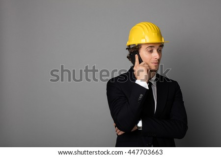 elegant man in suit with yellow protection helmet on gray background with empty space talking at cellphone and giving information