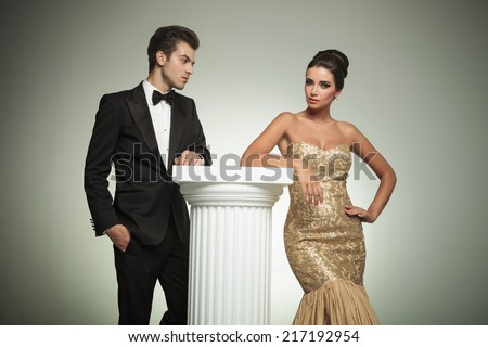 elegant man in tuxedo looking at her sexy woman posing in studio - stock photo