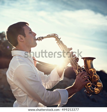elegant man play the saxophone on beach in summer day