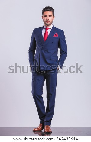 elegant man posing full body on studio background with hands in pockets - stock photo