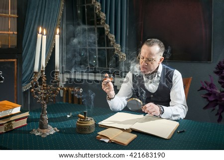 Elegant man sitting at a desk and looks through a magnifier in book