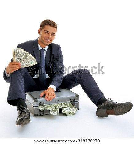 Elegant man sitting on case with money isolated on white - stock photo