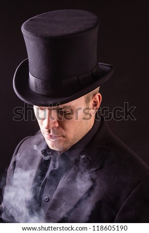 Elegant man standing in smoke in darkness