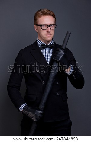 elegant man wearing a bow and holding umbrella - stock photo