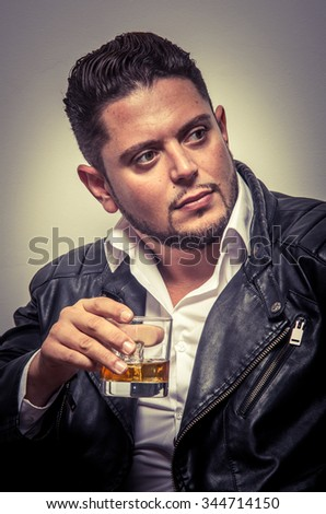 Elegant man with black leather jacket drinking a whiskey in studio - stock photo
