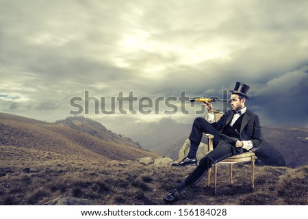 elegant man with cylinder looks through a telescope sitting on a chair in the mountain - stock photo