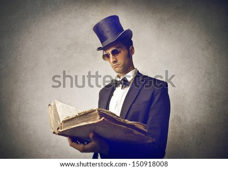 elegant man with cylinder reads old book