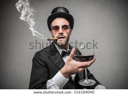 elegant man with cylinder smokes a cigar and drinks red wine - stock photo