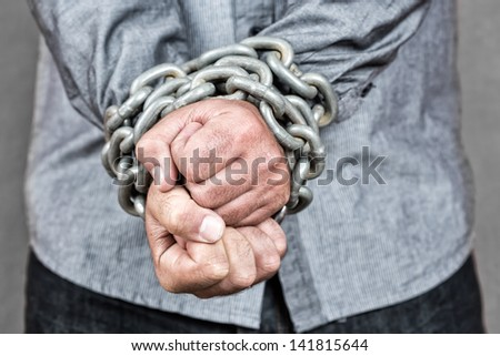 Elegant man with his hands chained with strong steel chains and a padlock - stock photo