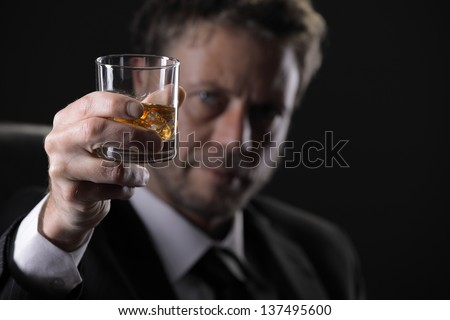 Elegant mature man drinking whiskey against black background