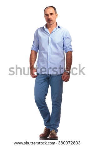 elegant mature man with open shirt posing hands down while looking at the camera in white isolated studio background