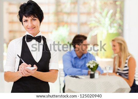 elegant mature waitress working in restaurant