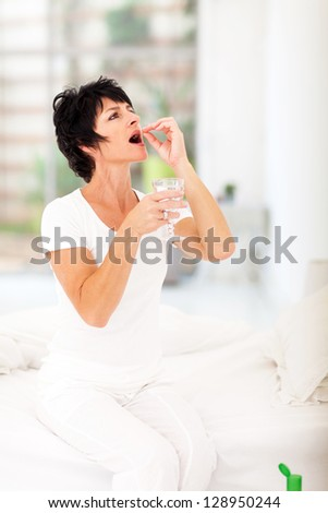 elegant mature woman taking pills at home