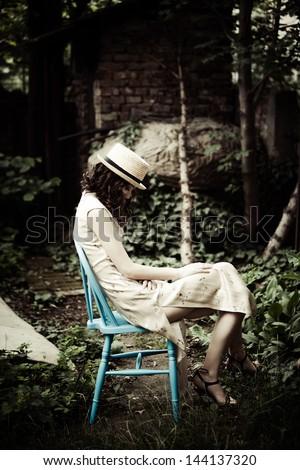 elegant melancholic  woman sit in garden - stock photo