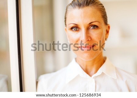 elegant middle aged businesswoman closeup portrait in office - stock photo