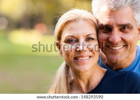 elegant middle aged couple closeup portrait outdoors - stock photo