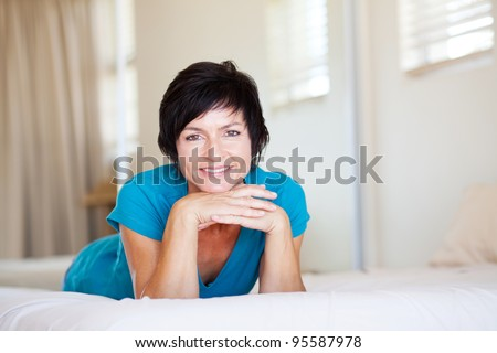 elegant middle aged woman lying on bed relaxing - stock photo