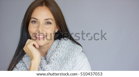 Elegant middle aged woman posing with woolen warm scarf
