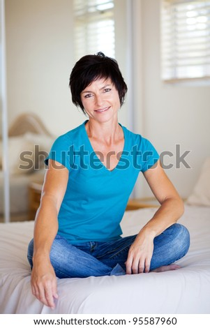 elegant middle aged woman sitting on bed - stock photo
