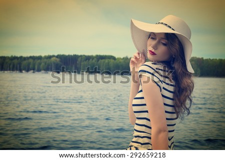 elegant model posing , she has a white hat , looking down with sea water on background . long hair in a summer day.vintage color