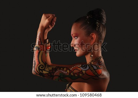 Elegant model with a lot of jewelry on the black background - stock photo