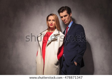 elegant modern couple standing together against studio wall with hands in pockets