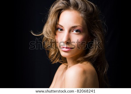 Elegant, moody portrait of beautiful young brunette on black background. - stock photo