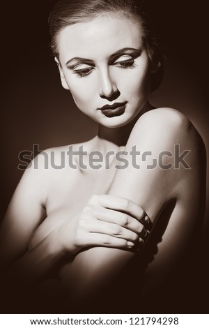 Elegant naked young woman posing over dark blue background. Light and shadow. - stock photo
