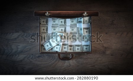 Elegant open briefcase filled with dollar packs on a wooden desktop in the dark, top view - stock photo