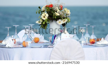 Elegant Outdoor Wedding Table with Sea View. Table set for an event party or wedding reception. Wedding Chairs and covers at an outdoor wedding.  - stock photo
