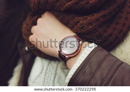 Elegant outfit. Closeup of brown wrist watch on the hand of stylish woman. Fashionable girl on the street. Female fashion. Toned  - stock photo