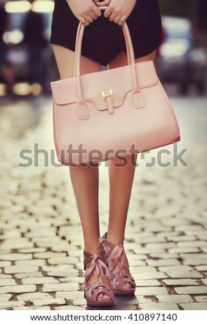 Elegant outfit. Closeup of leather bag in hands of stylish woman. Fashionable girl posing on the street. Female fashion. City lifestyle. Toned - stock photo