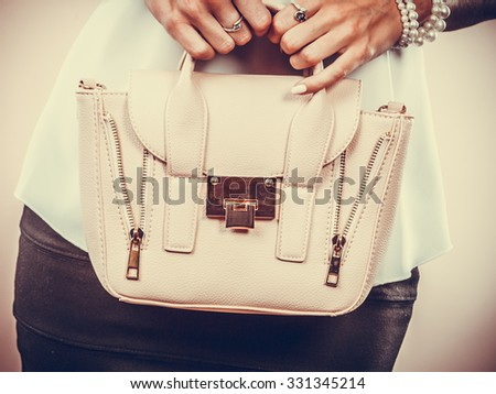 Elegant outfit. Female fashion. Girl in fashionable clothes holding bag handbag.