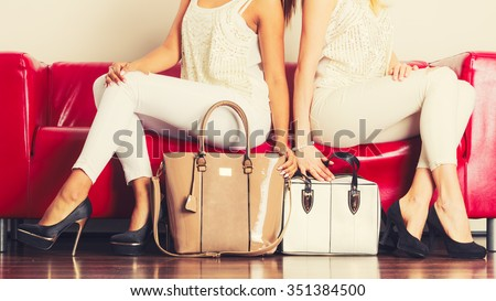 Elegant outfit. Female fashion. Two women wearing fashionable clothes high heels with bags handbags sitting on red couch.