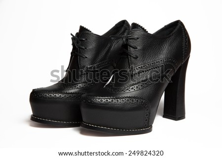 Elegant pair of woman's black leather battalions (ankle bootie) shoes isolated on a white background  - stock photo