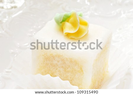 Elegant petit four with glaze frosting and yellow rose on decorative plate.  Macro with extremely shallow dof. - stock photo