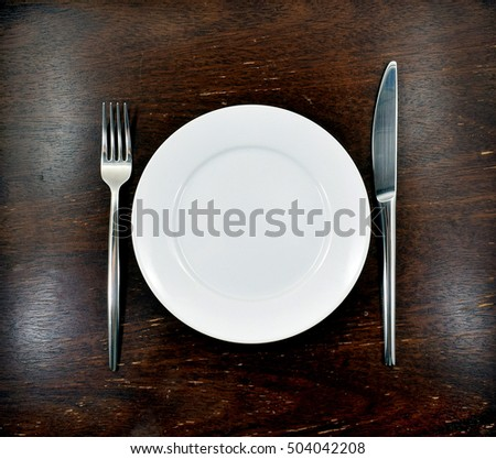 Elegant place setting with styling silverware (fork and knife) on textured wood table