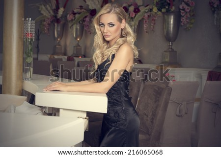elegant pretty woman in black evening dress waiting alone at the restaurant bar .looking in camera - stock photo