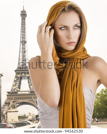 elegant pretty young woman with a long scarf and a lighter dress. She looks at left with the scarf on the head and she touches the hair with right hand - stock photo
