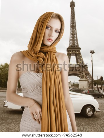 elegant pretty young woman with a long scarf and a lighter dress. She looks in to the lens and has the scarf on the head, the right hand is on her belly. - stock photo