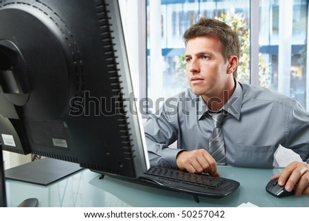 Elegant professional businessman working on computer looking at screen with hand on mouse in sunlit office.