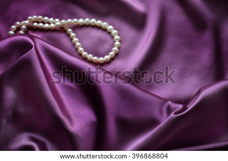 Elegant purple background with silk and pearls