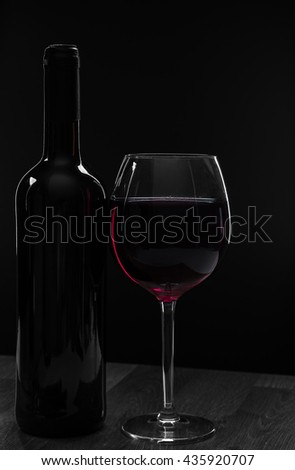 Elegant red wine glass and a wine bottle on a wooden table