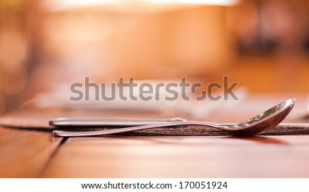 Elegant restaurant setting in high key of cutlery on a table setting - stock photo