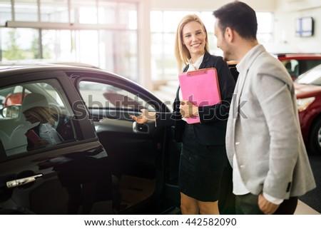 Elegant salesperson working at car dealership - stock photo