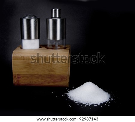 Elegant salt and pepper shakers on black background - stock photo