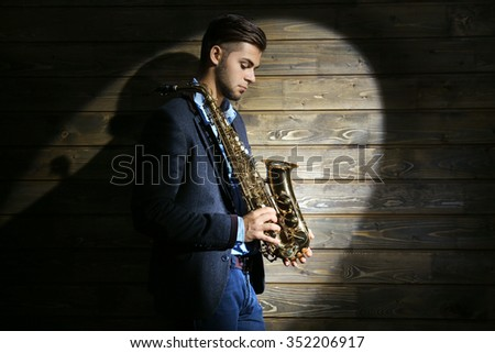 Elegant saxophonist plays jazz on wooden background