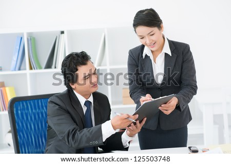 Elegant secretary bringing some documents for signature to her boss - stock photo